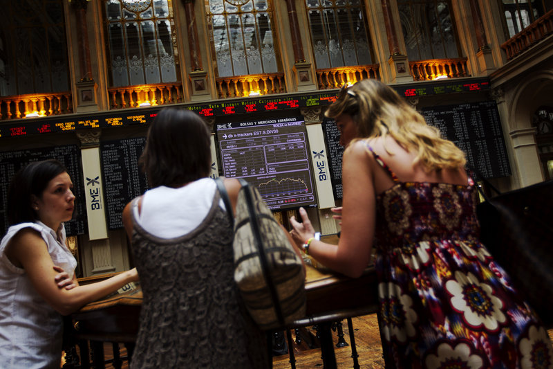 Women talk in front of the main screen at the Madrid Stock Exchange during volatile trading last week. Spain's finance minister insists her country is in no need of a bailout, but a potential default by Greece, Spain and Italy has undercut the banking system across the eurozone.