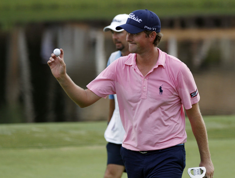 Webb Simpson acknowledges the crowd after sinking a 5-foot eagle putt on the 15th hole during the third round of the Wyndham Championship at Greensboro, N.C. Simpson shot a 6-under 64 to pull into a two-stroke lead.