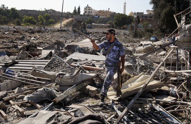 A Hamas security official inspects damage at a training camp after an Israeli airstrike in Gaza City on Sunday, as diplomats scrambled to keep violence from escalating.