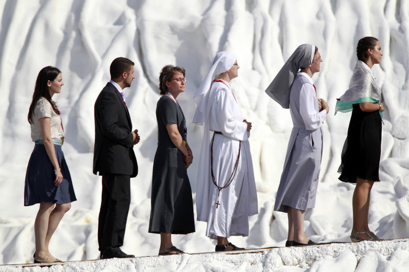 Worshippers line up to receive communion Sunday from Pope Benedict XVI during a Mass at an airfield near Madrid.