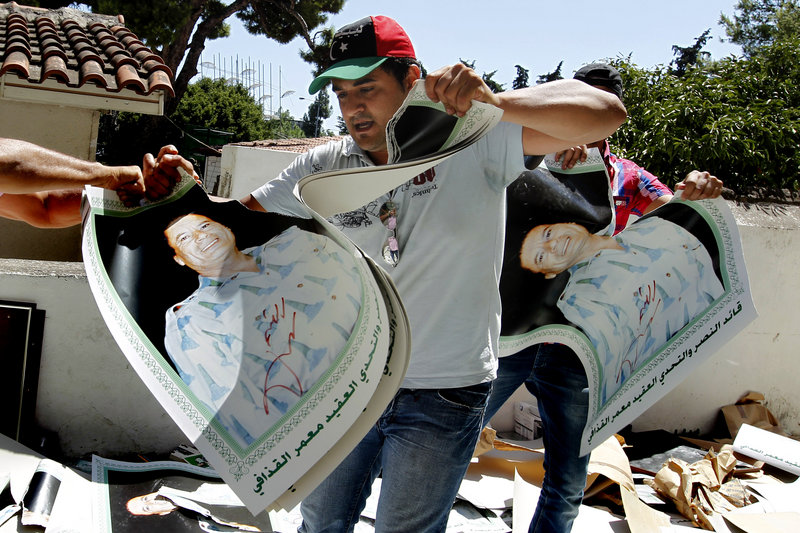 Libyans living in Greece rip posters of Moammar Gadhafi during a protest at Libya's consulate in Athens.