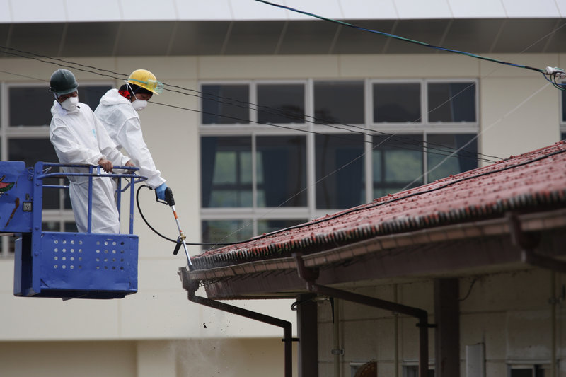 Workers decontaminate a gutter around the roof of Yasawa Kindergarten in Minami-Soma, about 12 miles from the tsunami-crippled Fukushima Dai-ichi nuclear facility, earlier this month. Radiation levels are expected to remain high at many sites near the power plant.
