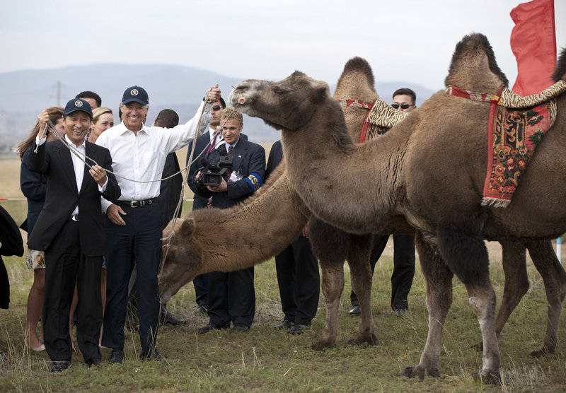 Vice President Joe Biden and Mongolian Prime Minister Sukhbaatar Batbold, left, pose for pictures with camels at a Mongolian wrestling performance in Ulan Bator on Monday.