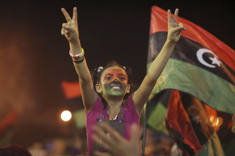 People celebrate what they believe is nearly the end of the military conflict against Gadhafi's regime in the rebel-held eastern city of Benghazi, Libya, early today.