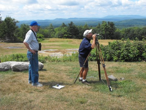 Dick Anderson and Earl Raymond use a surveying instrument at Hacker's Hill to identify the landforms and mountain ranges and piece together the geological history of the landscape. A geology walk and talk will be held Tuesday from 5:30 to 6:30 p.m. Rain date is Thursday.