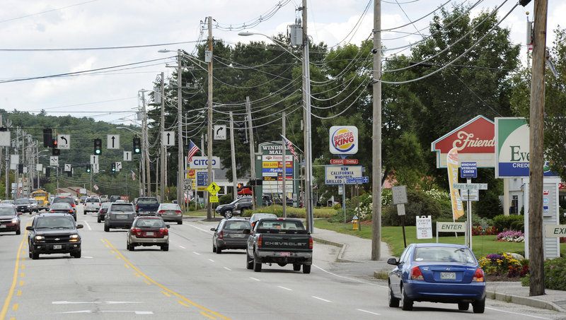Traffic moves along Route 302 in North Windham. The Planning Board wants to see downtown buildings with pitched roofs, landscaped parking lots, and brick walls, clapboard siding or shingles.