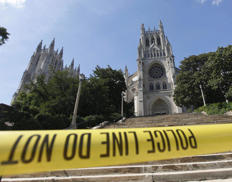 Police tape cuts off access to the National Cathedral in Washington on Tuesday after a piece of the left spire on the tower at right broke off when a 5.8-magnitude earthquake rumbled across much of the East Coast.