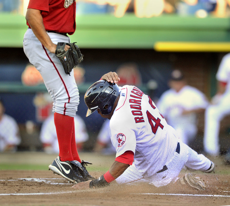 Reynaldo Rodriguez of the Portland Sea Dogs slides across the plate Tuesday night, scoring on a wild pitch in the second inning. It was the only run for Portland; the Harrisburg Senators emerged with a 4-1 victory before a sold-out Hadlock Field crowd.