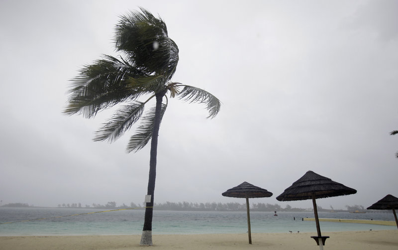 Palm trees bend as rain and wind from Hurricane Irene hit a beach Wednesday in the Bahamian capital of Nassau. Irene was a Category 4 storm Wednesday night, with winds up to 135 mph.