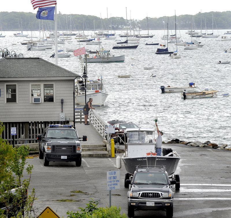 Boat owners haul their vessels from the water at Falmouth Town Landing on Thursday. Hundreds of watercraft moored here and all along the coast are potentially threatened by the approaching Hurricane Irene, which is on a track to reach Maine as early as Sunday.