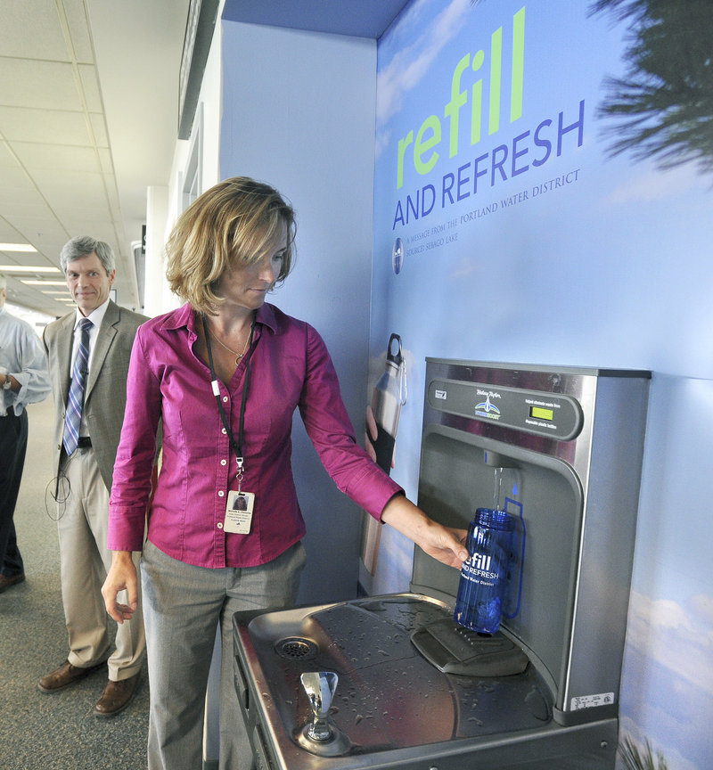 Paul Bradbury, director of the Portland International Jetport, looks on as Michelle Clements of the Portland Water District fills a water bottle after water district and airport officials teamed up to install a water bottle filling station inside the security area at the terminal.