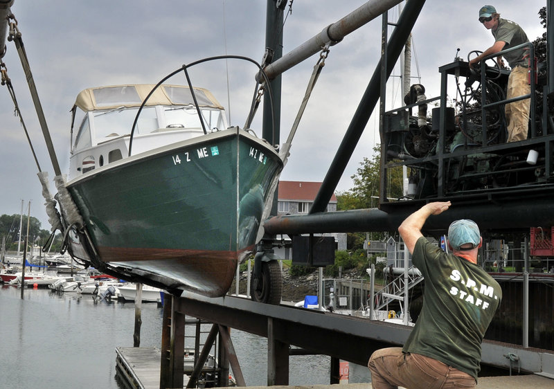 South Port Marine's Paul Morin directs Adrian Link as they pull boats from Portland Harbor on Thursday.