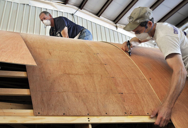 Carpenters Bill Harjula and Jeff Mank work on the hull of a new boat at Lyman-Morse Boatbuilding in Thomaston.