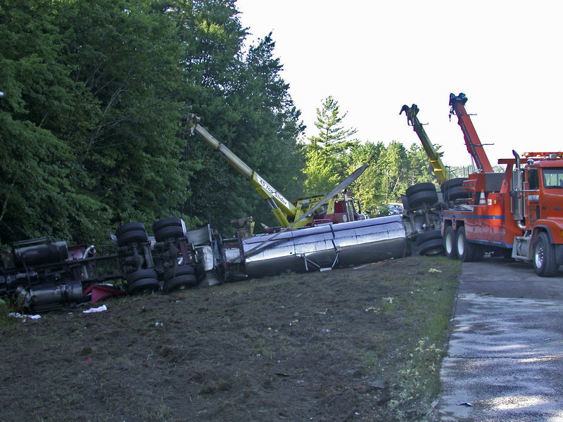 Traffic is detoured as wreckers work to right a tanker truck that skidded sideways to avoid a collision and rolled over into a ditch on Route 111 at Spruce Street in Lebanon on Friday. Ambulances transported two people to H.D. Goodall Hospital in Sanford with non-life-threatening injuries.
