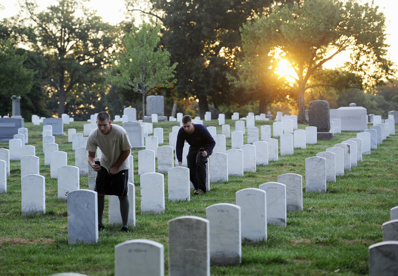 Soldier of the Army Old Guard photograph headstones at Arlington National Cemetery at sunrise on Wednesday. Their work will help update and fully digitize the cemetery's maps.