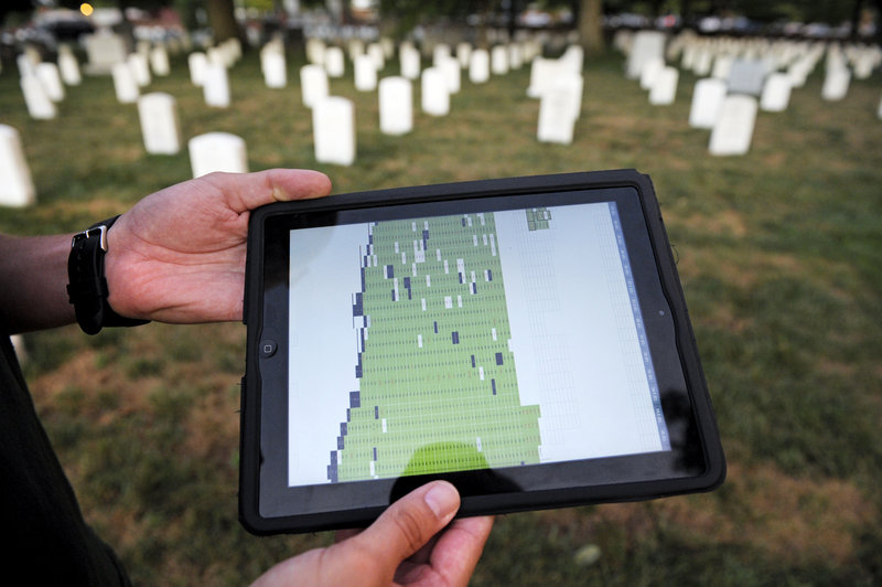 "Army Spc. Matthew Caruso shows the Apple iPad and spreadsheet that is used to keep track of which headstones the Old Guard has photographed. Caruso said, ""it's a good feeling"" to do the work, ""but it can be pretty stressful."""