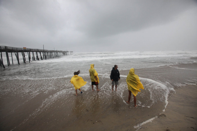 From left, Sophie Waterfield, Skylr Peele, Chloe Waterfield and Tim Waterfield look out at the ocean waves near the Frisco, N.C., pier as the first storm bands from Hurricane Irene arrive Friday. By evening, 50 mph winds were raking the North Carolina coast.