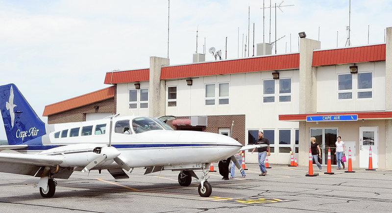 Passengers walk from a terminal gate to a Cape Air plane at the Augusta State Airport last week. The airline flies several trips a day between there and Boston s Logan Airport.