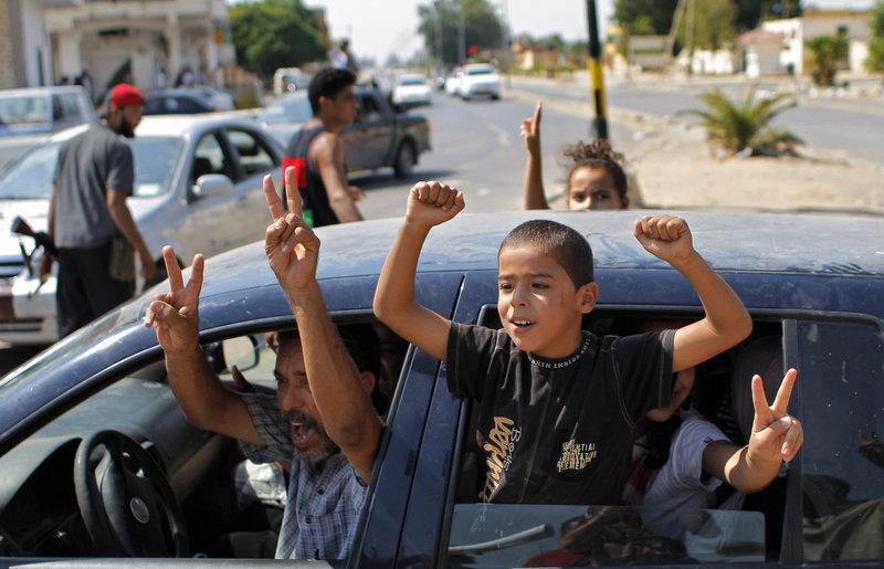 Libyans celebrate the liberation of their district, Qasr bin Ghashir in Tripoli, on Saturday. Much of the city, however, lacks power and water and is littered with garbage and wreckage.