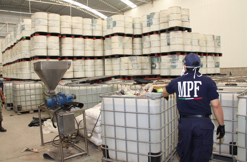 A federal police officer looks at drums of chemicals to make methamphetamine, seized in June in Mexico.
