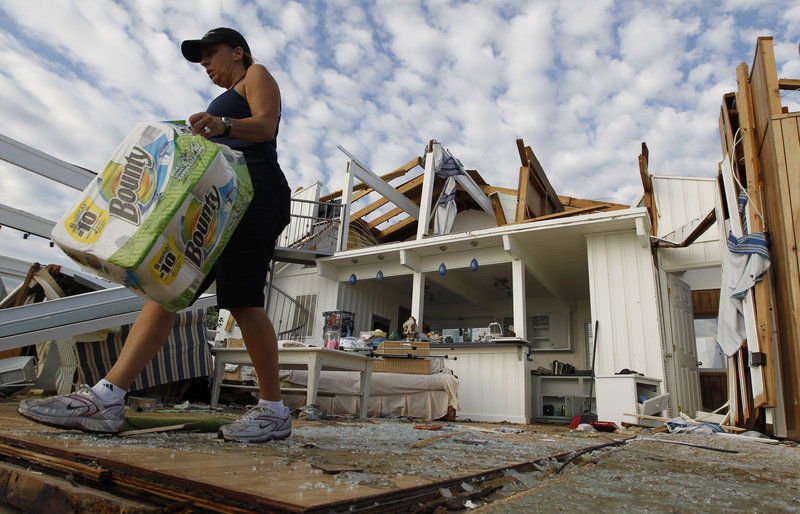 Denise Robinson clears out her destroyed beach home in Virginia Beach, Va., on Sunday after Hurricane Irene struck. Officials speculate that a tornado swept through.