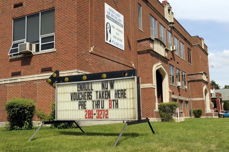 A sign at Our Lady of Hungary Catholic School in South Bend, Ind., encourages students to enroll using school vouchers. It's a scenario that public school advocates have long feared.
