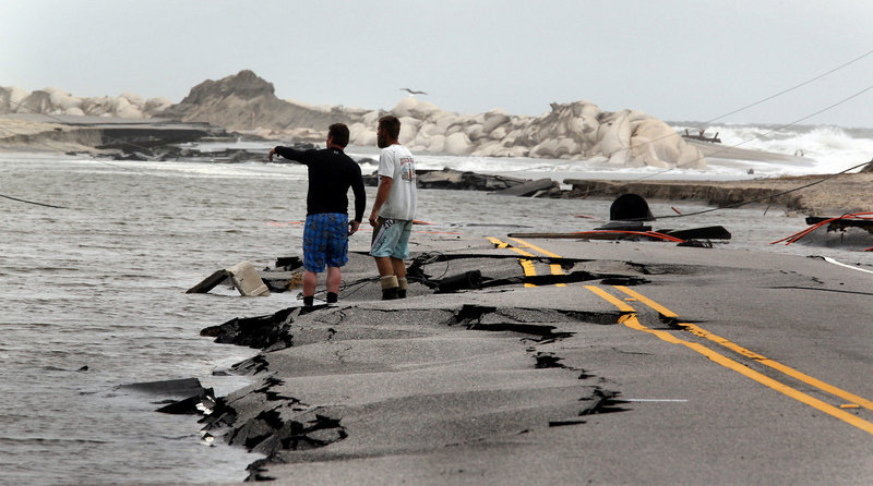 Workers try to find a telephone line Tuesday along Highway 12 in Rodanthe, N.C. Meanwhile, at least 2,500 residents were stranded on remote Hatteras Island. Customers along the East Coast have been warned to be prepared for lengthy outages until floodwaters recede and crews can safely enter and restore service.