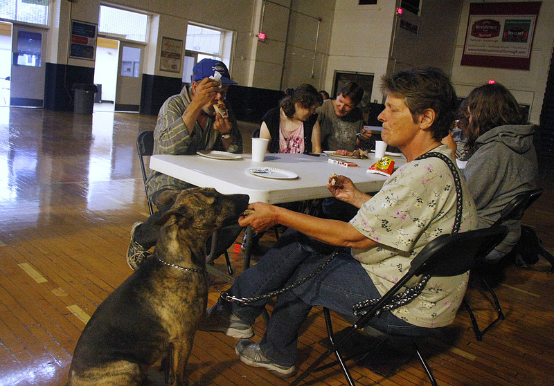 Patricia Steffens of Portland shares a bite of her sandwich with her dog, Sadie, while spending the day at the shelter at the Portland Expo today while waiting out the storm.