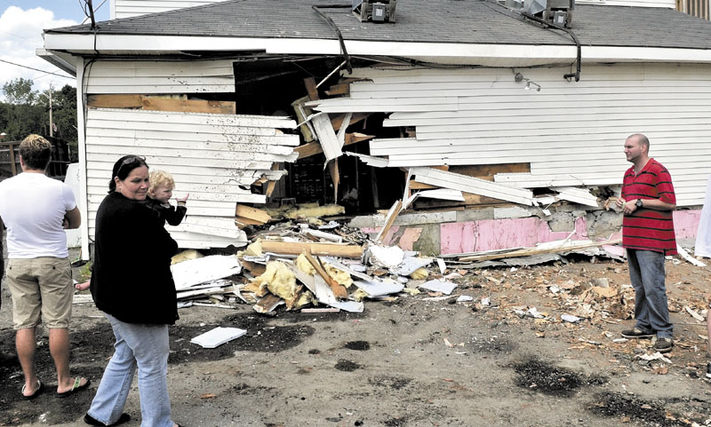 Brenda DiMeo carries a child while she and family members survey the damage to their Cambridge General Store after a loaded pulp truck lost control and crashed into the building around 4 a.m. Tuesday. No one was hurt, but the store on Route 150 sustained extensive damage, and a parked car was destroyed by the rolling logs, said police.