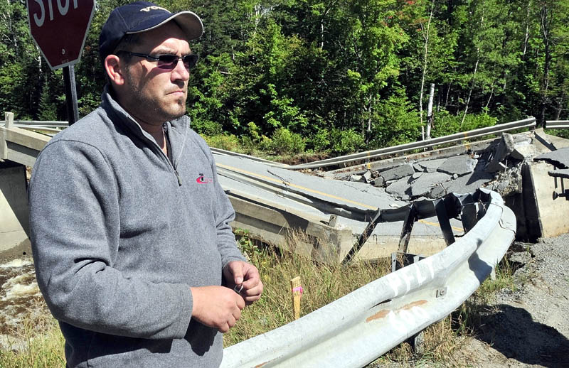 CLOSE CALL: Truck driver Yannick Livernoche of Canada on Monday talks beside a collapsed bridge over the Carrabassett River on Route 27 in Carrabassett Valley. During tropical storm Irene on Sunday Livernoche and his truck became trapped between the bridge and another nearby collapsed bridge leaving his rig unable to drive away until the bridges are repaired.