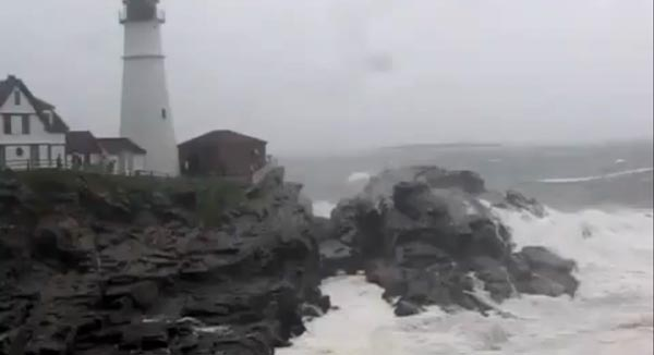 Waves break over the rocks below the keepers quarters at Portland Head Light.