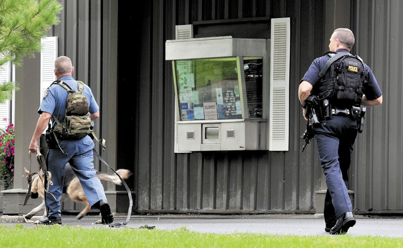 SEARCH: A Maine state trooper with a tracking dog and Waterville police Sgt. Dan Ames search outside HealthFirst Federal Credit Union in Waterville on Thursday after a male reportedly armed with a knife robbed the credit union.