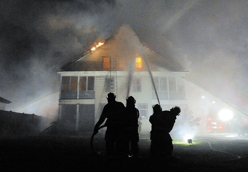 BATTLING: Firefighters from the Waterville and Winslow fire departments responded to a blaze at an apartment building on Water Street in Waterville Monday night.