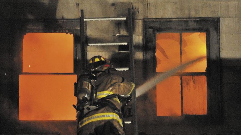 TEAMING UP: Firefighters from the Waterville and Winslow fire departments responded to a blaze at an apartment building on Water Street in Waterville Monday night.