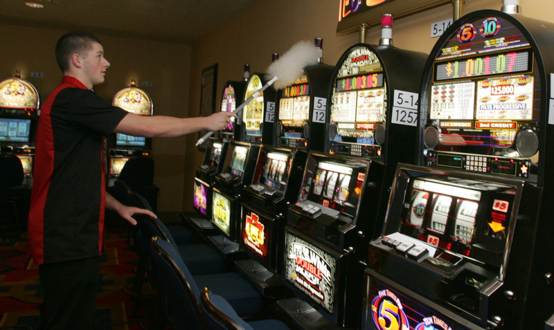 A casino porter dusts some of the 475 slot machines at Hollywood Slots in Bangor. Maine legislators need to set ground rules for who gets to build casinos, where they are built and who benefits from the proceeds -- rather than allowing the gambling industry to act as it sees fit.