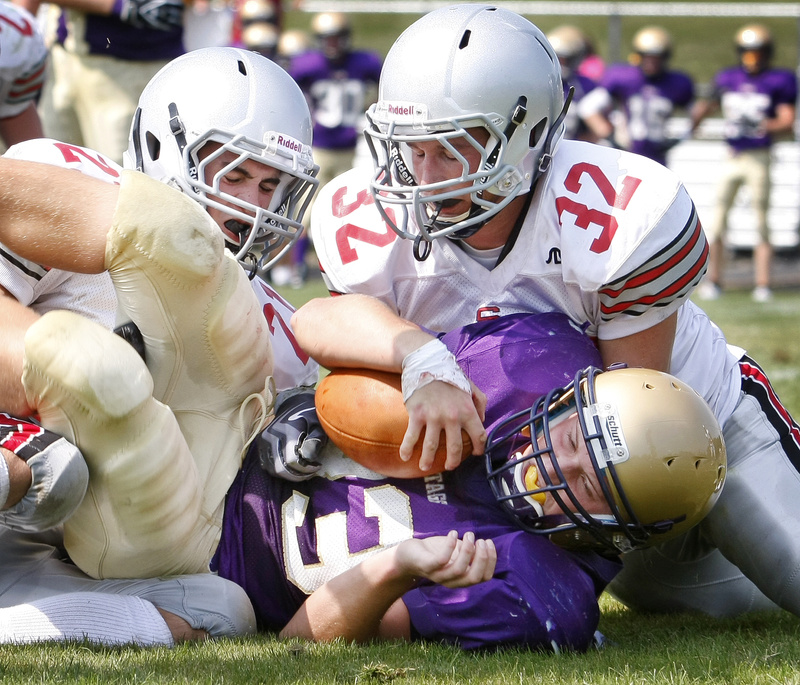 Brent Green, 33, of Cheverus is brought down by South Portland's Logan Gaddar, 21, and Dan Medici, 32, during the second quarter today at Cheverus. The Stags pulled away for a 59-21 win.