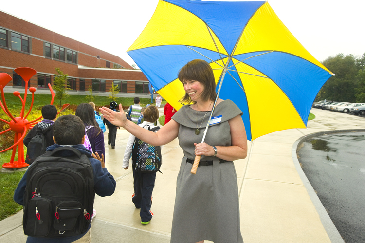 Beverly Coursey, principal at the new Ocean Avenue Elementary School in Portland, greets arriving students today.