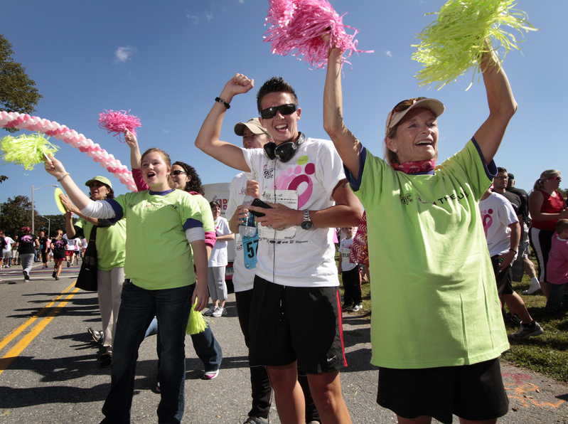 Sherman Kendal of Falmouth, right,, Alley Smith of Lewiston and Katelyn LaBreck of Standish cheer for fellow runners at the Race for the Cure on Back Cove today.