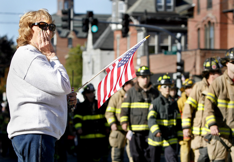 Jeannine Sullivan of Portland wipes away tears as Maine firefighters walk up Congress Street during the city of Portland's observance of the 10th anniversary of 9/11 today. Sullivan said she would have marched in the procession but she has a leg problem that would have caused her pain.