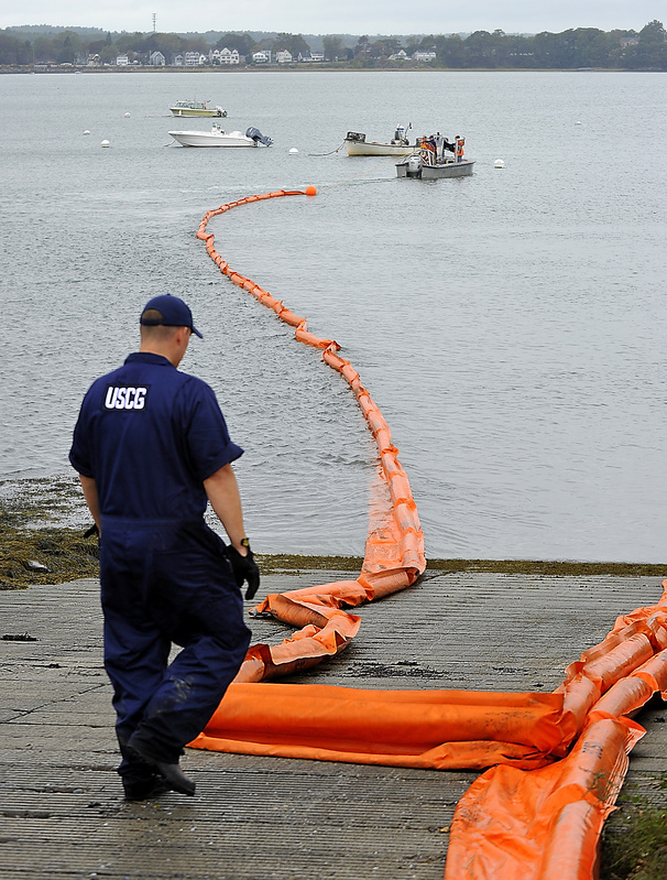 Brian Wereda of the US Coast Guard assists as a boat pulls a 500-foot harbor boom from the shore of Portland's Back Cove Tuesday, during an oil spill readiness exercise organized by the Coast Guard and the Maine DEP.
