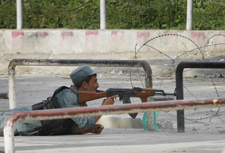An Afghan policeman takes position near the building occupied by militants, unseen, in Kabul, Afghanistan today.