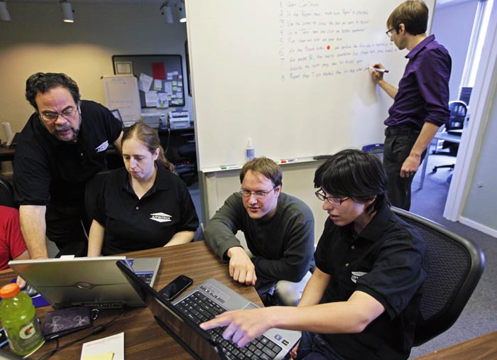 Aspiritech co-founder Moshe Weitzberg, standing left, works with employees – seated from left, Katie Levin, Rick Alexander and Jamie Specht, as they test a new program in Highland Park, Ill.