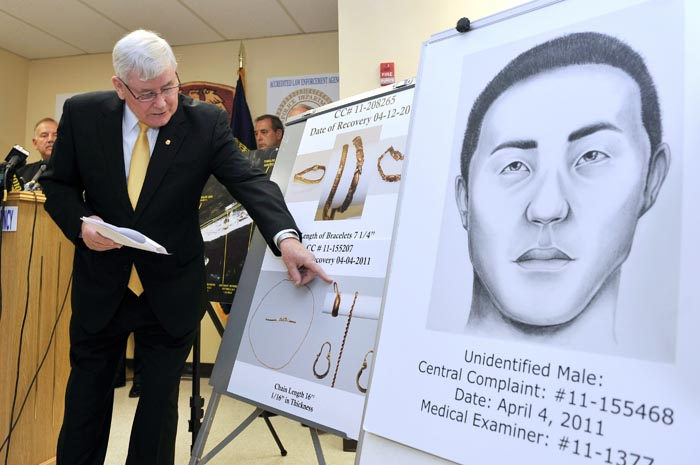 Suffolk County Police Commissioner Richard Dormer points out photographs of jewelry recovered from bodies found along Ocean Parkway in Suffolk County at a news conference today in Yaphank, N.Y. At right is a drawing of an unidentified male body found.