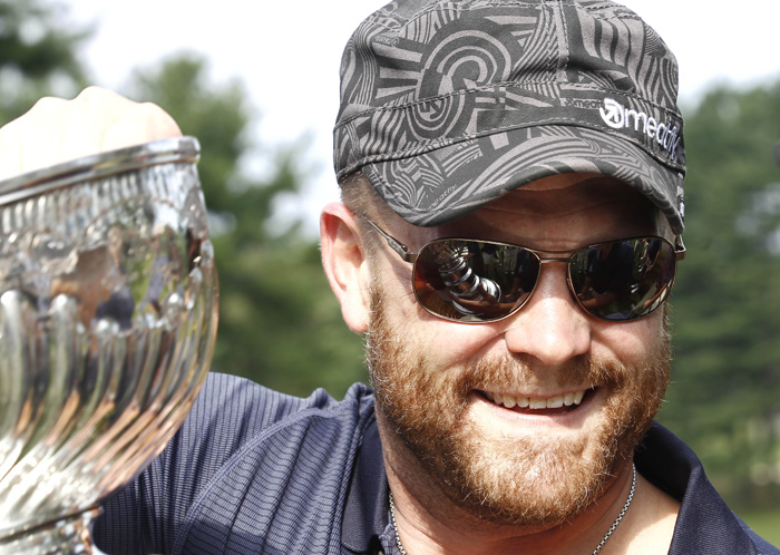 Boston Bruins goaltender Tim Thomas carries the Stanley Cup during a golf tournament in Bolton, Mass., recently.