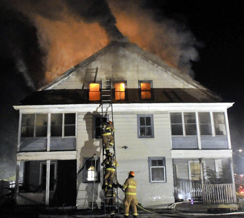 Staff photo by Michael G. Seamans Firefighters from Waterville and WinslowFire Departments responded to a structure fire on Water Street Monday evening. The apartment building was a total loss.