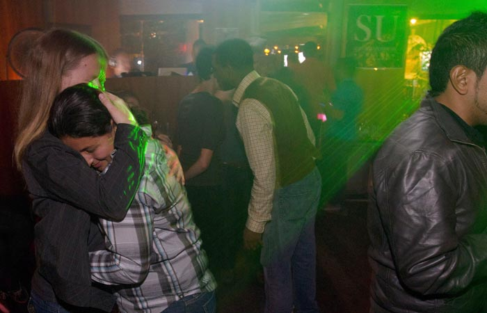 A woman who is active-duty in the Navy embraces her partner after midnight during a celebration for the end of the policy commonly known as