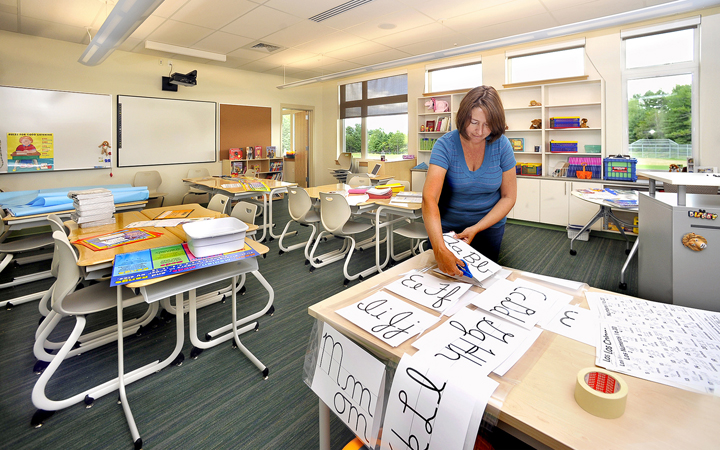 Fourth-grade teacher Stacey Sawyer cuts out her new alphabet as she prepares her classroom for opening day recently at Great Falls Elementary School in Gorham.
