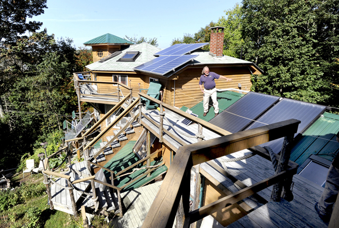 Michael Mayhew shows some of the solar panels atop his Boothbay Harbor home's many roof lines. The home will be included in Saturday's green building open house tour.