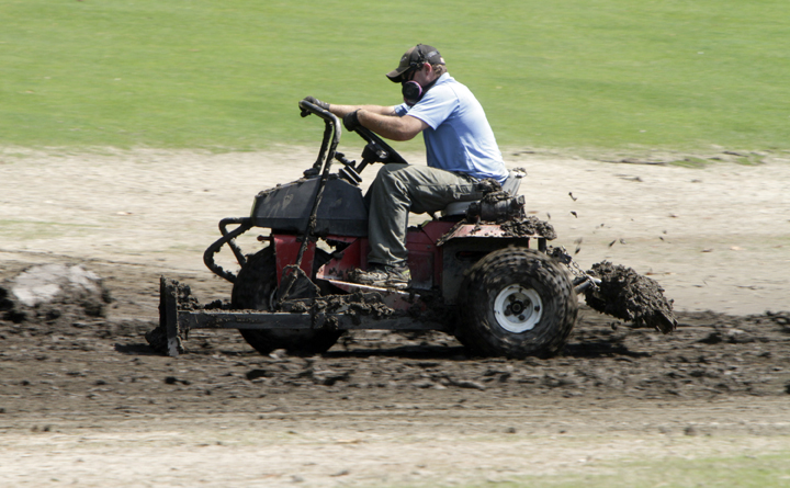 Scott Burton tries to move mud off the golf course at the Woodstock Inn resort today in Woodstock, Vt.