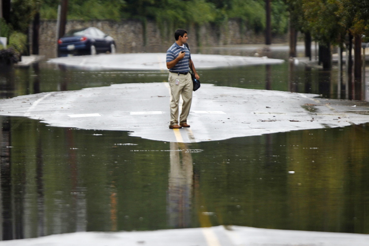 A person turns back from crossing floodwaters today in the Manayunk neighborhood of Philadelphia. In Pennsylvania, inundated communities were evacuated today and state offices closed down because of the rising waters.